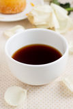 Tea. White cup of tea with rose petals Stock Image