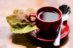 Tea. Cup of tea sitting on a wood table with a leaf Royalty Free Stock Image