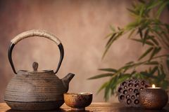 Tea. Black iron asian teapot and burning candle,vintage style Royalty Free Stock Image