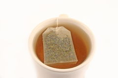 Tea. Green tea bag in a cup brewing on white background Royalty Free Stock Images