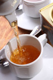 Tea. Pore from a pot into a cup Royalty Free Stock Photo