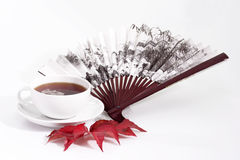 Tea. A cup of tea with fan and autumn leafs on bright background Stock Photography