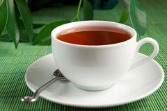 Tea. A cup of fresh tea on green background Stock Images