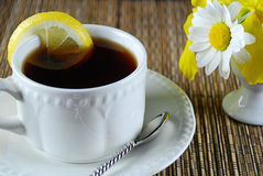 Tea. A fresh hot cup of tea with lemon by spring flowers royalty free stock image
