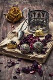 Tea accessories amid frayed books. Old book is strewn with the tea leaves on wooden background,tinted in vintage style Royalty Free Stock Image