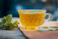 Tea of Ajwain, Trachyspermum ammi in a transparent cup with some leaves of ajwain good for health, skin and for weight loss. Stock Photo