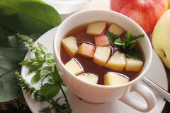 Tea with apples. Black tea with cut apples and mint Royalty Free Stock Photo