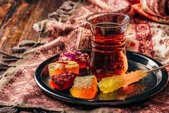 Tea in armudu with oriental delight. Tea in armudu glass with oriental delight rahat lokum on metal tray over wooden surface and tablecloth stock images