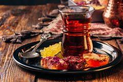 Tea in armudu with oriental delight. Tea in armudu glass with oriental delight rahat lokum on metal tray over wooden surface and tablecloth royalty free stock images
