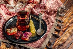 Tea in armudu with oriental delight. Tea in armudu glass with oriental delight rahat lokum on metal tray over wooden surface and tablecloth royalty free stock photos
