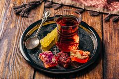 Tea in armudu with oriental delight. Tea in armudu glass with oriental delight rahat lokum on metal tray over wooden surface and tablecloth royalty free stock photography