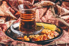 Tea in armudu with oriental delights and crystal sugar. Black tea in armudu glass with candies with different nuts and crystal sugar on metal tray over stock photos