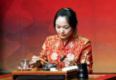 Tea art of China. A Chinese girl in traditional dress is performing tea art. China has history of tea culture for more than one thousand years Royalty Free Stock Images