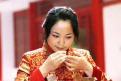 Tea art of China. A Chinese girl in traditional dress is performing tea art. China has history of tea culture for more than one thousand years Stock Image