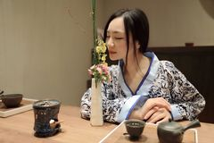 Tea art of China. A Chinese girl in blue hanfu dress is performing tea art. China has history of tea culture for more than one thousand years.Chinese tea set on Royalty Free Stock Image