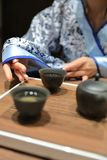 Tea art of China. A Chinese girl in traditional dress blue hanfu is performing tea art. China has history of tea culture for more than one thousand years.Chinese Royalty Free Stock Photography