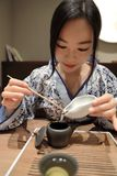 Tea art of China. A Chinese girl in traditional dress blue hanfu is performing tea art. China has history of tea culture for more than one thousand years.Chinese Royalty Free Stock Photo