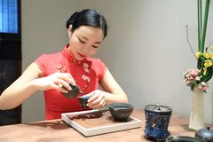 Tea art of China. A Chinese girl in traditional dress Red cheongsam is performing tea art. China has history of tea culture for more than one thousand years Stock Image