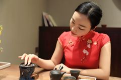Tea art of China. A Chinese girl in traditional dress Red cheongsam is performing tea art. China has history of tea culture for more than one thousand years Stock Photos