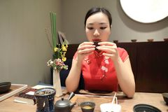 Tea art of China,drink tea. A Chinese girl in traditional dress Red cheongsam is performing tea art. China has history of tea culture for more than one thousand Royalty Free Stock Photos