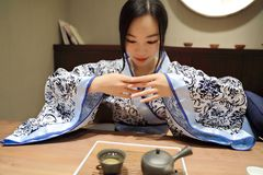 Tea art of China,drink tea. A Chinese girl in blue hanfu dress is performing tea art. China has history of tea culture for more than one thousand years.Chinese Stock Images