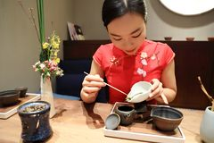 Tea art of China,make tea. A Chinese girl in traditional dress Red cheongsam is performing tea art. China has history of tea culture for more than one thousand Stock Photo