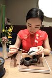 Tea art of China,make tea. A Chinese girl in traditional dress Red cheongsam is performing tea art. China has history of tea culture for more than one thousand Royalty Free Stock Photography