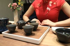 Tea art of China,make tea. A Chinese girl in traditional dress Red cheongsam is performing tea art. China has history of tea culture for more than one thousand Stock Photography