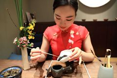 Tea art of China,make tea. A Chinese girl in traditional dress Red cheongsam is performing tea art. China has history of tea culture for more than one thousand Stock Photos
