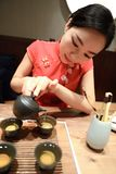 Tea art of China,pour tea. A Chinese girl in traditional dress Red cheongsam is performing tea art. China has history of tea culture for more than one thousand Royalty Free Stock Image