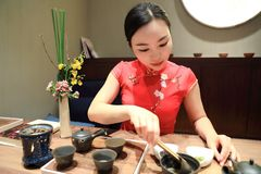 Tea art of China,pour tea. A Chinese girl in traditional dress Red cheongsam is performing tea art. China has history of tea culture for more than one thousand Stock Photography