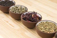 Tea assortment. Assortment of dry tea in ceramic bowls: green, black, herbal, flower tea sorts Stock Images