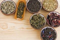 Tea assortment. Assortment of dry tea in ceramic bowls: green, black, herbal, flower tea sorts Royalty Free Stock Photo