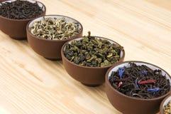 Tea assortment. Assortment of dry tea in ceramic bowls: green and black tea sorts Stock Photo