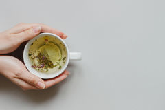 Tea background. Hands holding cup of hot green tea on the gray background, top view. Copy space Stock Images