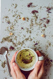 Tea background. Hands holding cup of hot tea. Dry herbal tea on the gray background, top view. Copy space Royalty Free Stock Photos