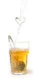 Tea bag. Pouring a heart of tea into a glass Stock Images