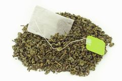 Tea bag. Inside a mount of dried green tea leaves Stock Images