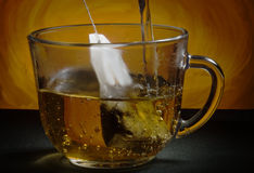 Tea bag. Glass cup on the table. Tea bag. Boiling water Royalty Free Stock Photos