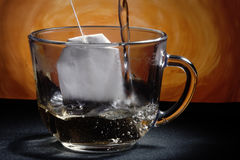 Tea bag. Glass cup on the table. Tea bag. Boiling water Royalty Free Stock Photo