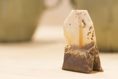 Tea bag. Standing wet used tea bag with mug in background Stock Photos