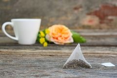 Tea bag on background of rose and and cup of tea. Tea bag on background of rose and and cup of tea on old wooden background Royalty Free Stock Photos