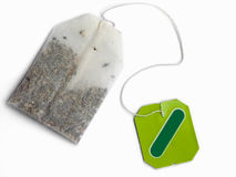 Tea bag with blank green label. Teabag with it's blank green label. Isolated on white Royalty Free Stock Image
