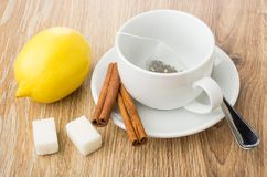 Tea bag in cup, cinnamon, lemon, lumpy sugar, teaspoon Royalty Free Stock Photography