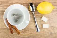 Tea bag in cup, cinnamon sicks on saucer, lemon, sugar Royalty Free Stock Photo