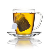 Tea Cup Bag. A glass cup of tea with a steeping tea bag isolated on a white background with a refection on the surface Royalty Free Stock Photo