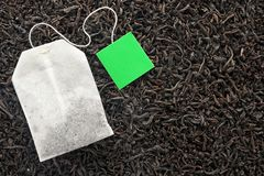 Tea bag on dry leaves, top view. With space for text royalty free stock photography
