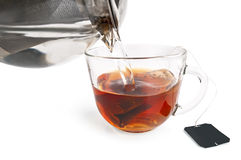 Tea from a bag in a glass cup with a teapot Royalty Free Stock Image
