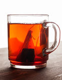 Tea bag in glass mug on wooden table royalty free stock photos