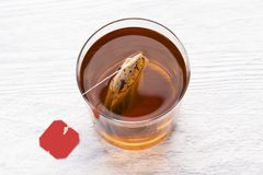 Tea bag in a glass cup with hot water on a white wooden table stock photo